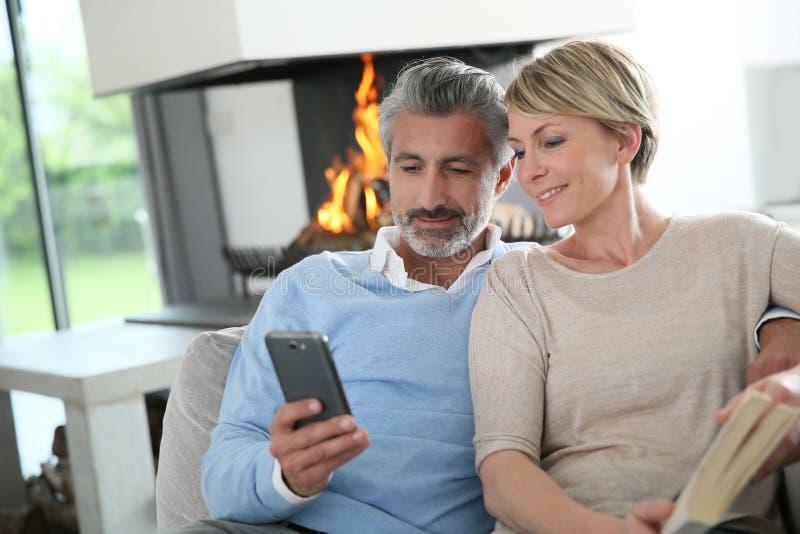 Paare von mittlerem Alter, die auf Sofa durch Kamin sitzen lizenzfreie stockfotos