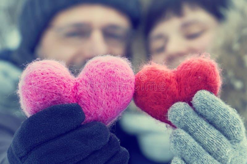Paare von mittlerem Alter, die draußen in den Händen zwei woolen Herzen halten lizenzfreie stockfotografie
