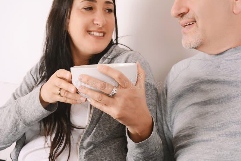 Paare von mittlerem Alter, die Popcorn essen und einen Film aufpassen stockbilder