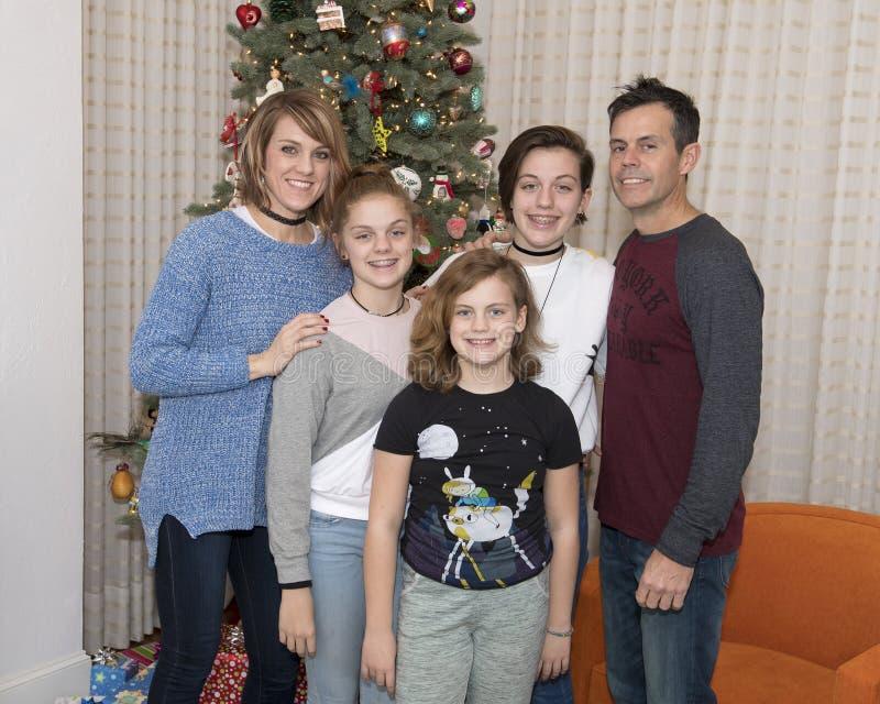 Paare von mittlerem Alter mit ihren 3 Töchtern, die vor einem Weihnachtsbaum stehen stockfotos