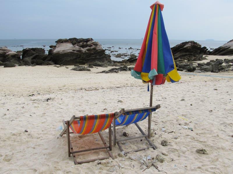 Paare von Sonnenruhesesseln und ein gefalteter Strandzeltstand auf dem Ufer eines einsamen Strandes stockfotos