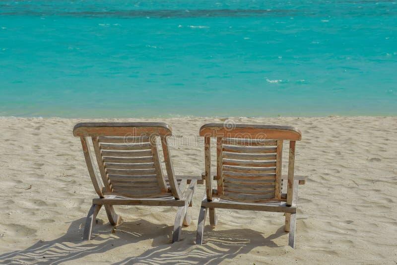 Paare von Stühlen auf dem schönen Strand in der Tropeninsel am Erholungsort stockfotografie
