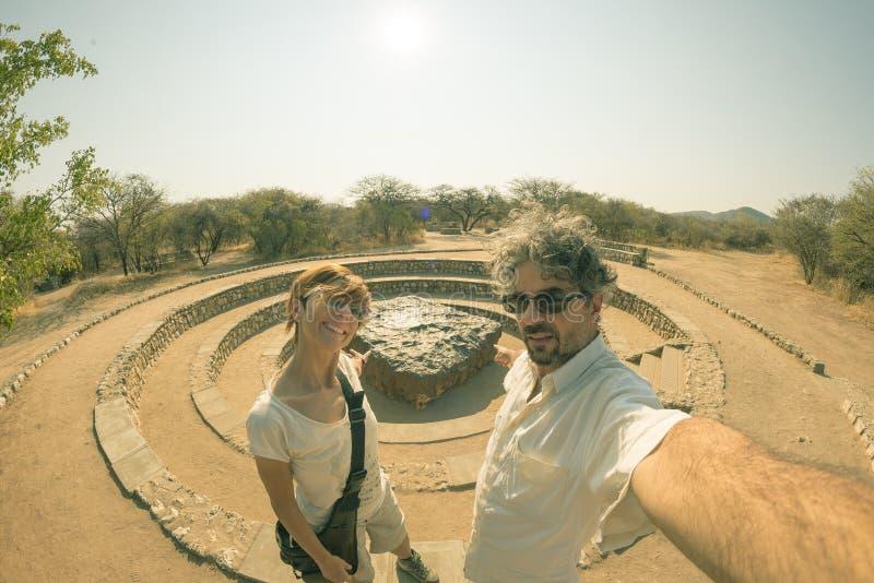 Paare von Touristen am Hoba-Meteoritstandpunkt, Namibia, Afrika Der Meteorit wird durch Schwermetalle mit hoher Dichte, größtente lizenzfreie stockfotos