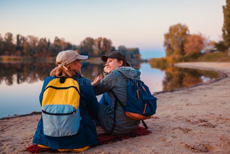 Paare von Touristen mit den Rucksäcken, die durch Herbstflussbank sich entspannen Sportive Frauen, die zusammen reisen Familien-Z lizenzfreie stockfotografie