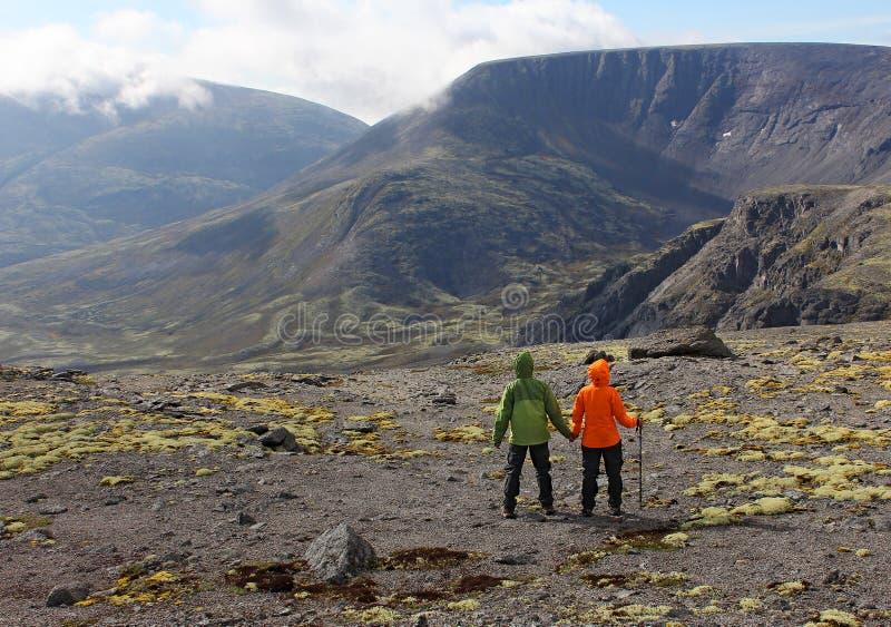 Paare von Touristen sind auf der Hochebene und bewundern die Berge stockbilder