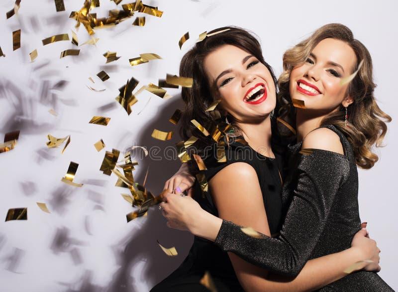 Paare von zwei Rich Women Laughing mit Kristall von Champagne luxus Party Zeit lizenzfreie stockfotografie