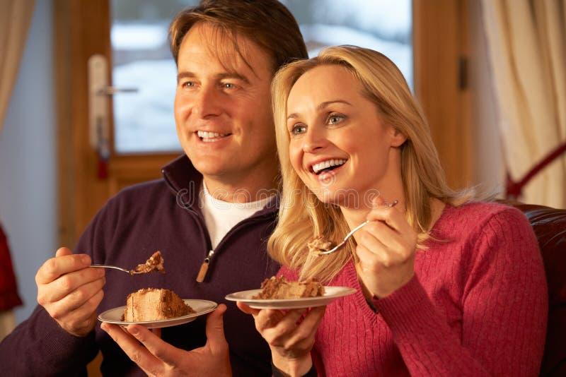 Paare, welche die Scheibe des Kuchens sitzend auf Sofa genießen lizenzfreie stockfotos