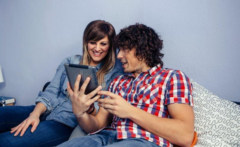 Paare, welche die Tablette betrachten stockfotos