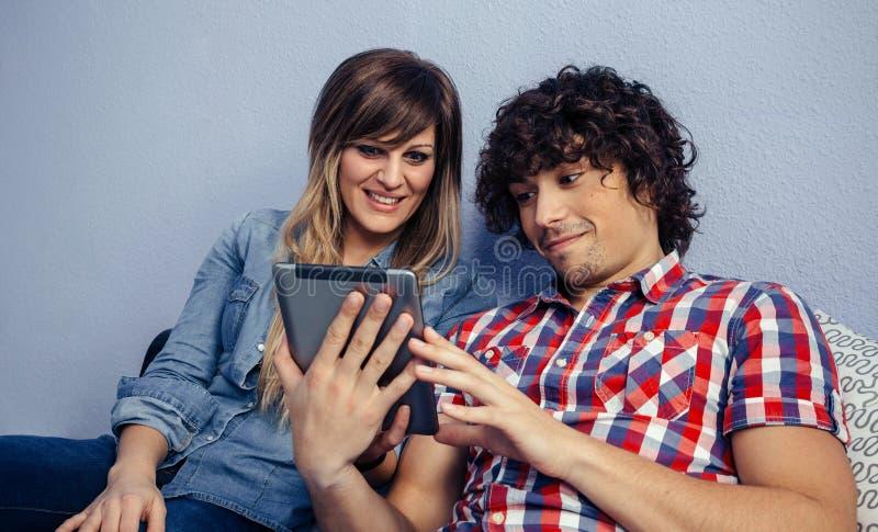 Paare, welche die Tablette betrachten stockbild