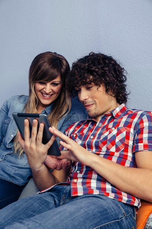 Paare, welche die Tablette betrachten lizenzfreie stockfotos