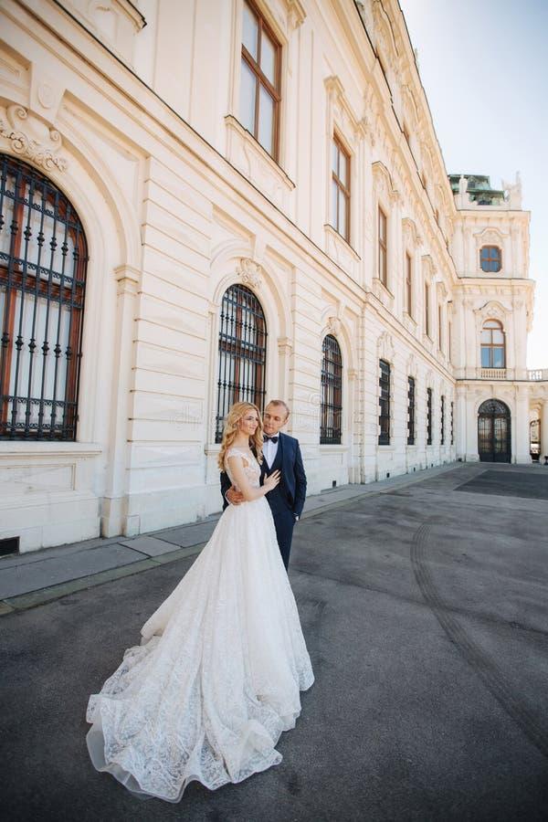 Paargang dichtbij het grote paleis Elegante bruidegom en bruid in hun huwelijkskleren Liefde royalty-vrije stock foto's
