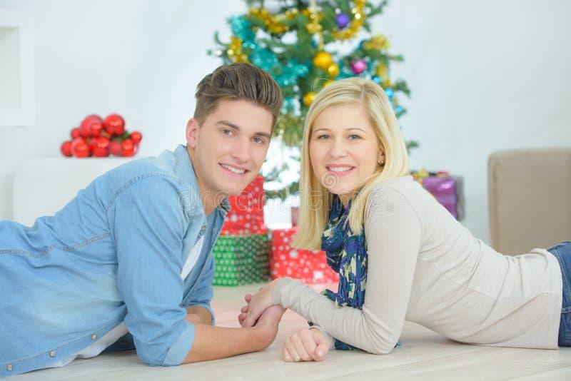 Paarhändchenhalten im vorderen Weihnachtsbaum stockfotos