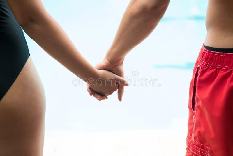Paarhändchenhalten am Poolside lizenzfreies stockfoto
