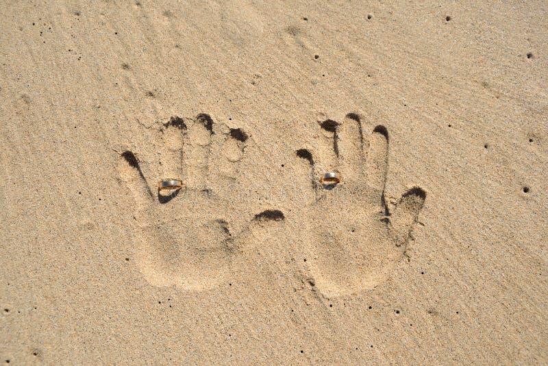 Paarhanddruck auf Sand mit Eheringen stockfotografie