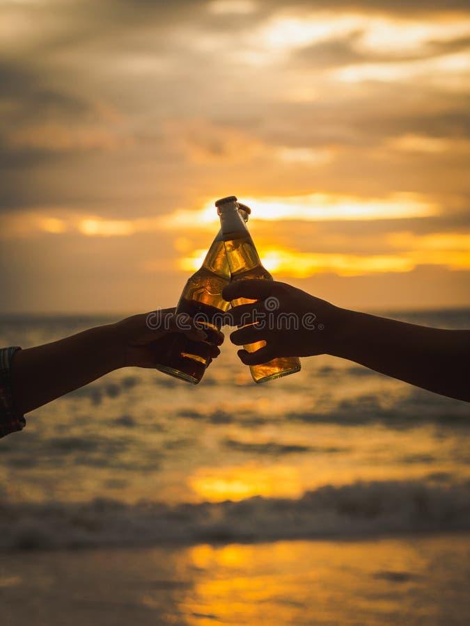 Paarhanden die bierflessen houden en op zonsondergangbea klinken stock afbeelding