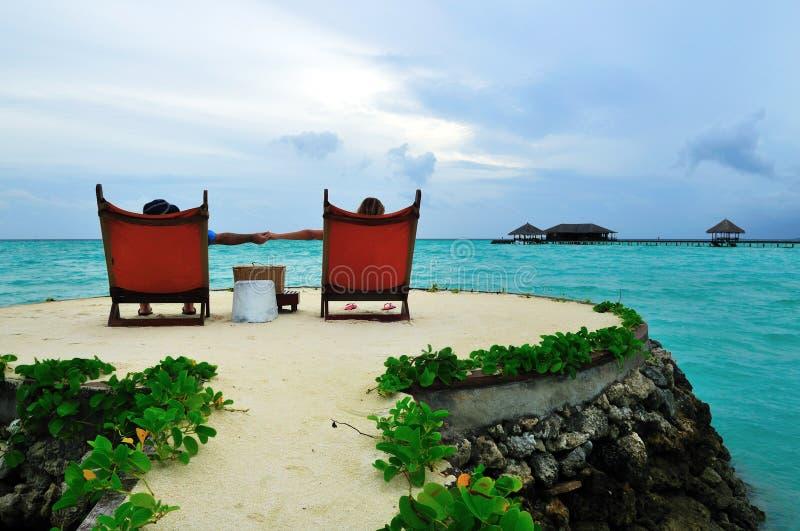 Paarholdinghände auf dem tropischen Strand stockbild