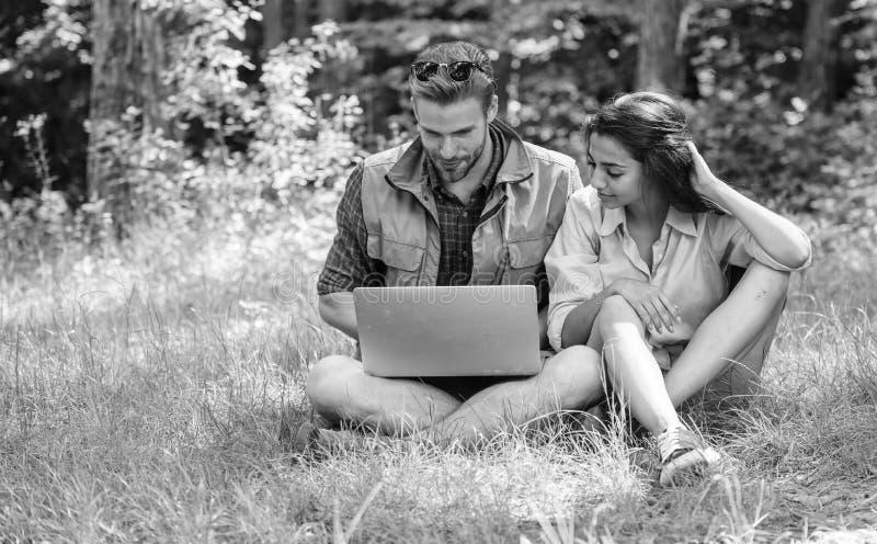 Paarjugend wendet Freizeit drau?en mit Laptop auf Mann und M?dchen, die Laptopschirm betrachten N?eher an Natur modern lizenzfreies stockbild