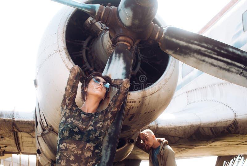 Paarkonzept Paarhaltung an der Retro- Fläche Paare der sinnlichen Frau und des gutaussehenden Mannes an den Flugzeugen Paare in d lizenzfreies stockbild