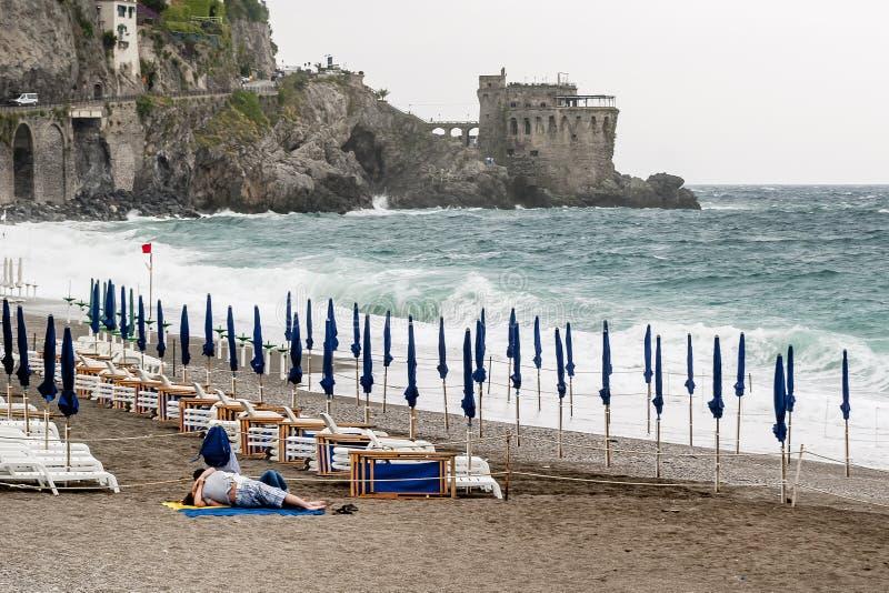 Paarkussen op Maiori-strand terwijl het overzees in onweer, Amalfi Kust, Campania, Italië is stock fotografie