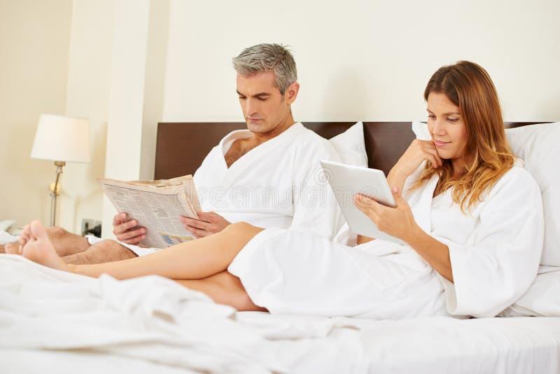 Paarlesungszeitung und ebook im Bett stockfoto
