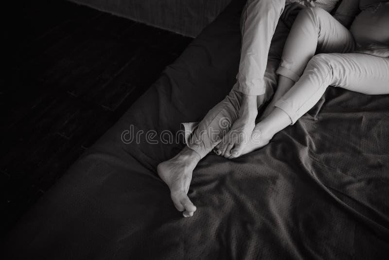 Paarliefde het liggen bed die naakte voeten koesteren stock fotografie