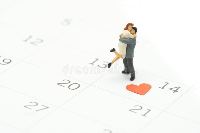 Paarminiatur2 menschen, die auf Kalender stehen Tag 14 trifft Valentine Day mit Herz geformtem rotem Papier Rotes Herz ist das Ve lizenzfreie stockbilder