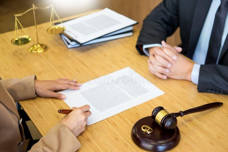 Paarprobleme, die einen Ehering-Richterhammer der Heirat goldenen entscheidet auf unterzeichnenden Scheidungsdokumenten der Heira stockfotos