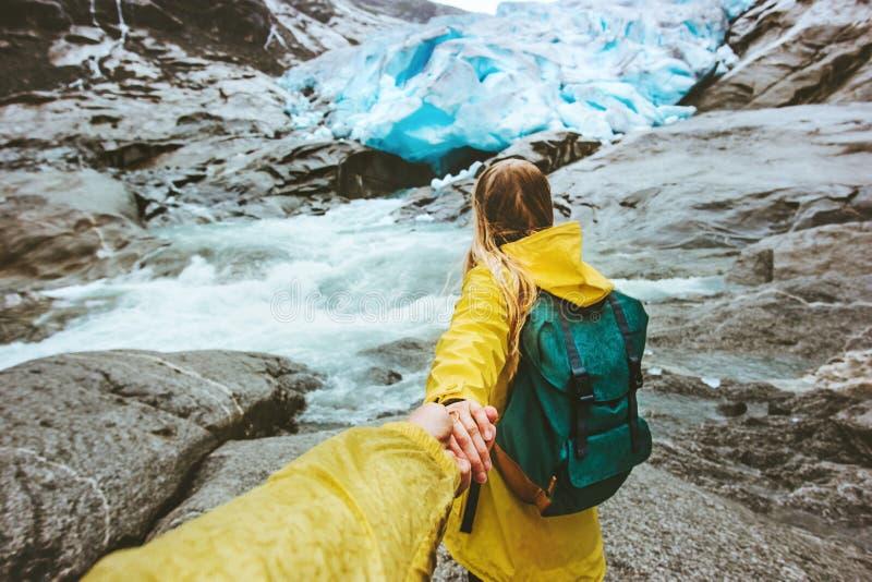 Paarreisende folgen Händchenhalten im Gebirgsgletscher stockfotos