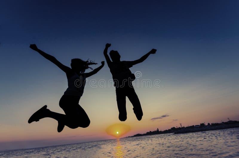 Paarsilhouet die bij zonsondergang op het strand springen stock foto's