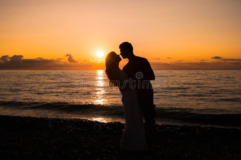 Paarsilhouet op het strand bij zonsondergang royalty-vrije stock afbeeldingen