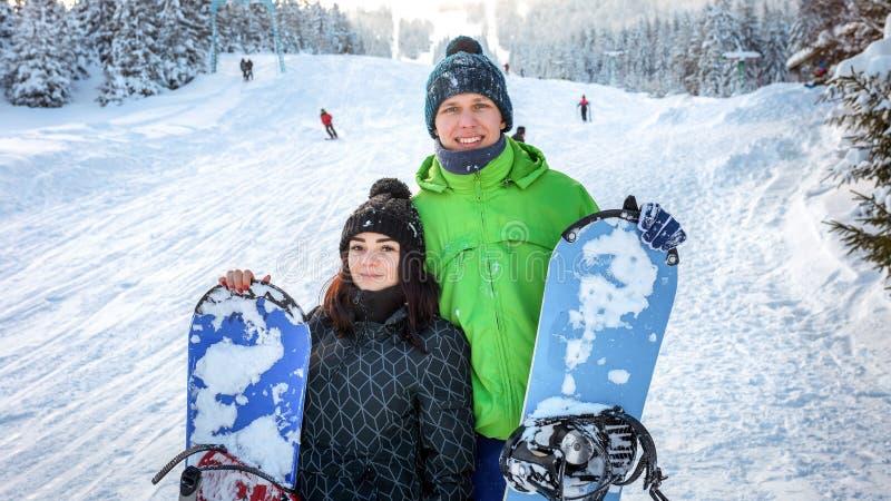Paarsnowboarder, die auf Skisteigung stehen stockfoto