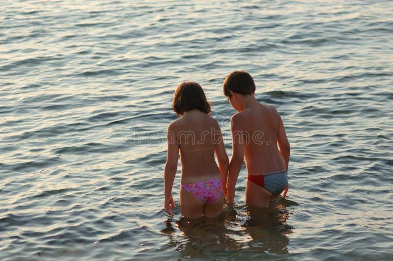 Paart Kind im Meer stockfotos