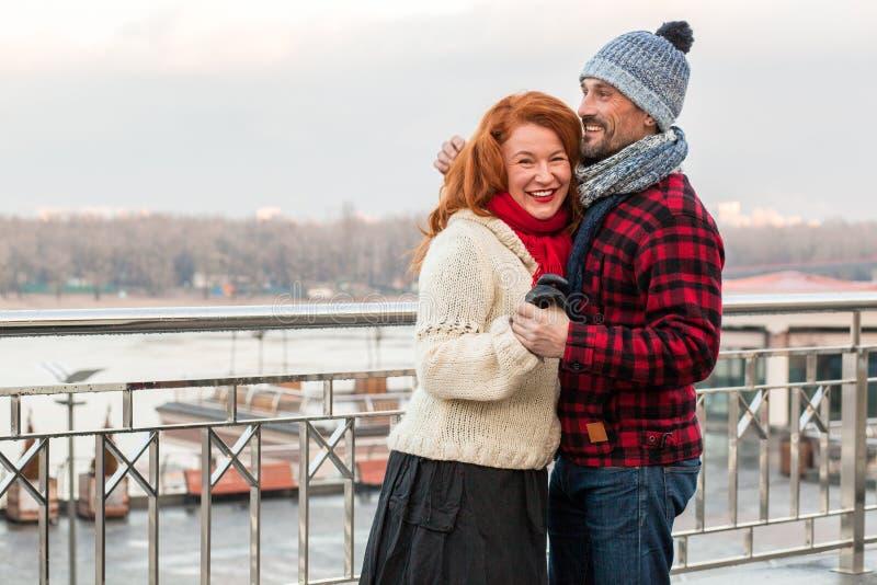Paartanzen auf der Brücke Lächelndes glückliches Paar, das nahe von der Sperre umarmt Tägliches Gehen der süßen Leuteliebe in Sta lizenzfreie stockbilder