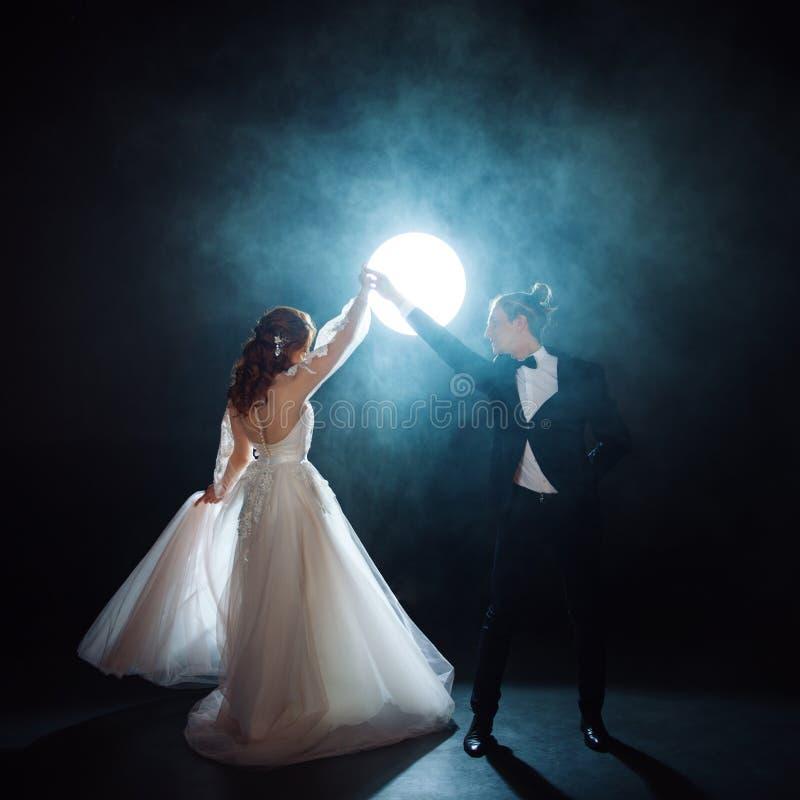 Paartanzen, die Braut und Bräutigam unter dem Mond Umarmungen zusammen Mann und Frau, Hochzeitskleid lizenzfreie stockfotos