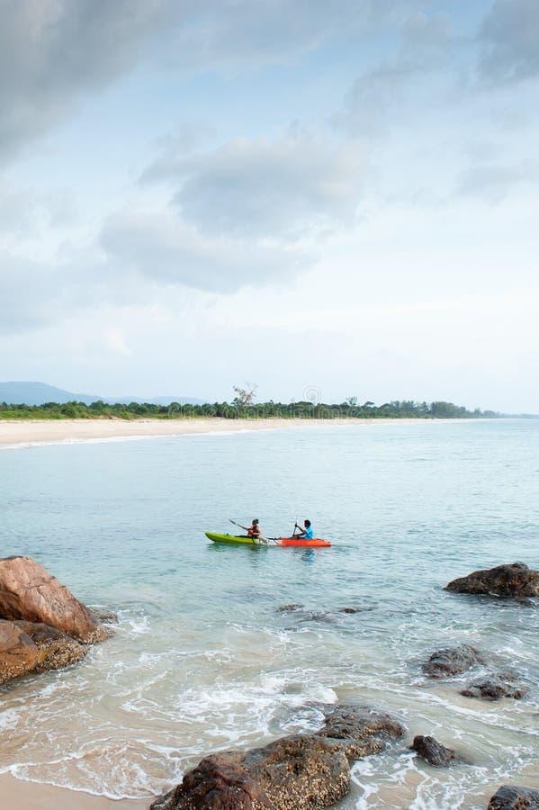 Paartoeristen die in tropische overzees kayaking Steen, rotsen, golven foregrounds, gebogen baai, bergen en bewolkte achtergronde stock afbeeldingen
