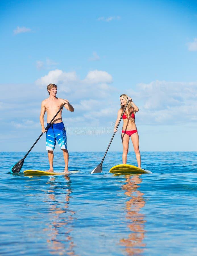 Paartribune die omhoog in Hawaï paddelen stock afbeelding