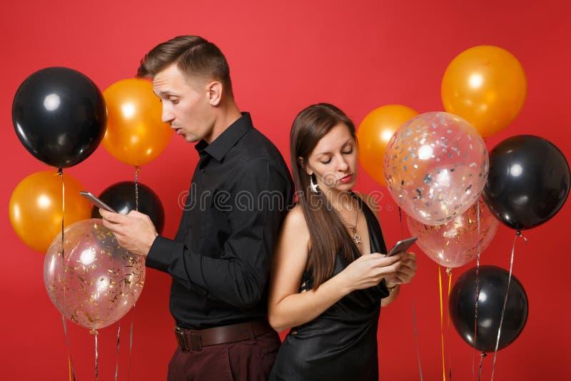 Paartribune terug aan achteroverseinen in de vakantiepartij van de cellphone vierende verjaardag die op rode lucht wordt geïsolee royalty-vrije stock foto's