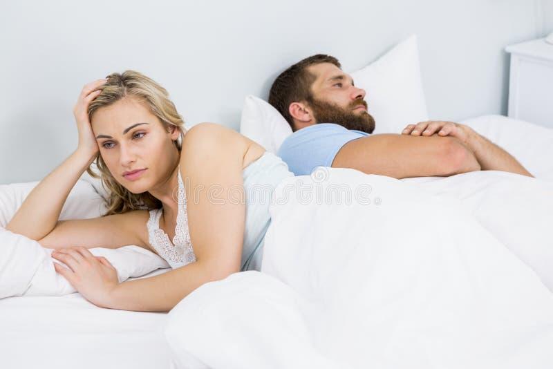Paarumkippen, das nachher einen Kampf auf Bett hat stockbild