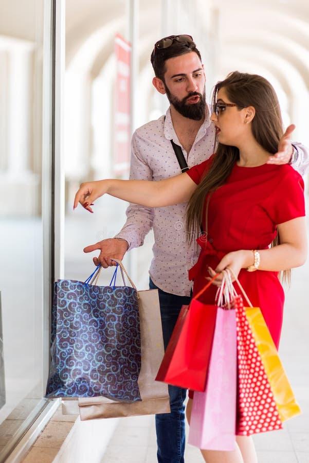 Paarvenster die in een winkelcentrum en het debatteren winkelen royalty-vrije stock afbeeldingen
