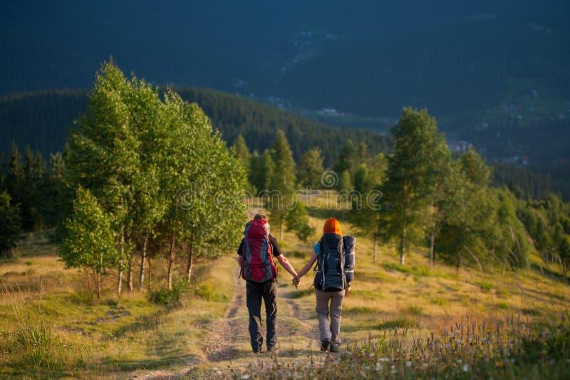 Paarwandelaars die met rugzakken handen houden, die in de bergen lopen royalty-vrije stock afbeeldingen