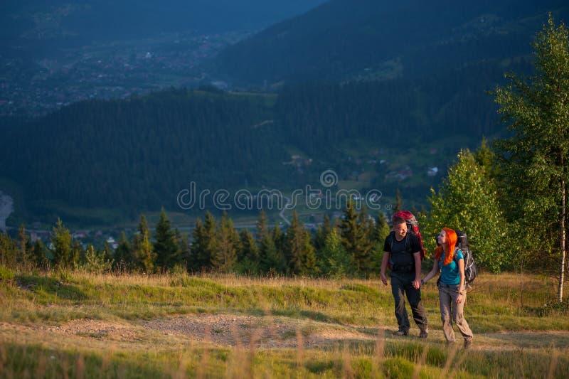 Paarwandelaars die met rugzakken handen houden, die in de bergen lopen stock foto