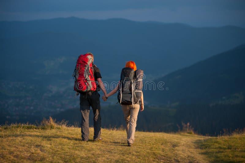Paarwandelaars die met rugzakken handen houden, die in de bergen lopen stock fotografie