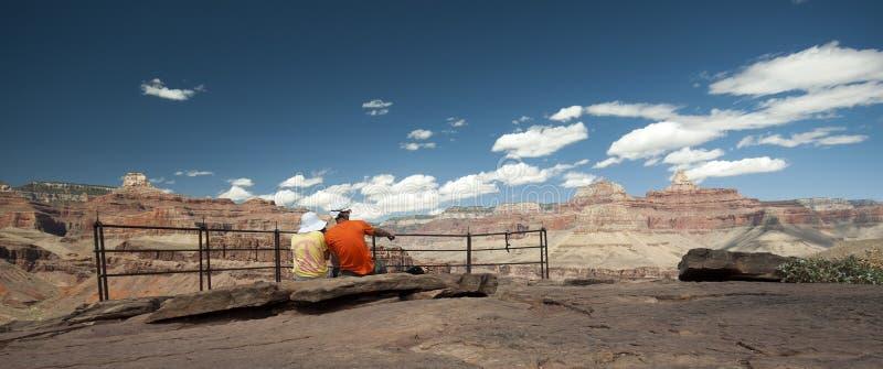 Paarwandelaars die van mening in Grand Canyon genieten stock afbeeldingen