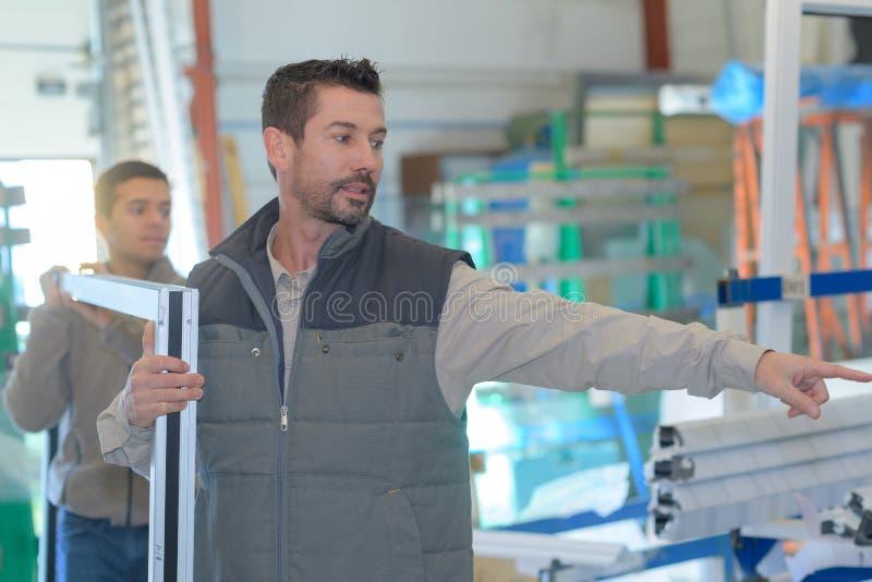 Paarwerklieden die raamkozijnen inspecteren bij fabriek binnen stock foto