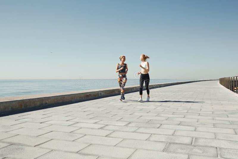 Paarwijfje die uitoefenend jogging gelukkig op waterkant lopen stock afbeeldingen