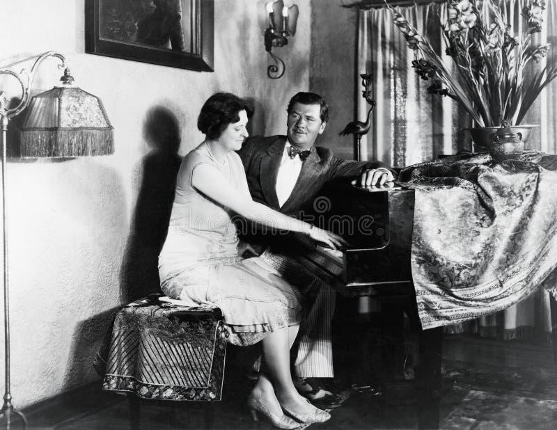 Paarzitting bij piano (Alle afgeschilderde personen leven niet langer en geen landgoed bestaat Leveranciersgaranties dat er zal z royalty-vrije stock afbeelding