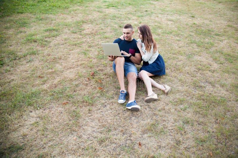 Paarzitting met laptop op gras stock foto