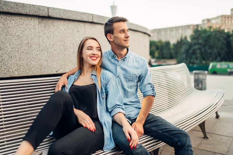 Paarzitting op de bank in het park van de de zomerstad stock foto's