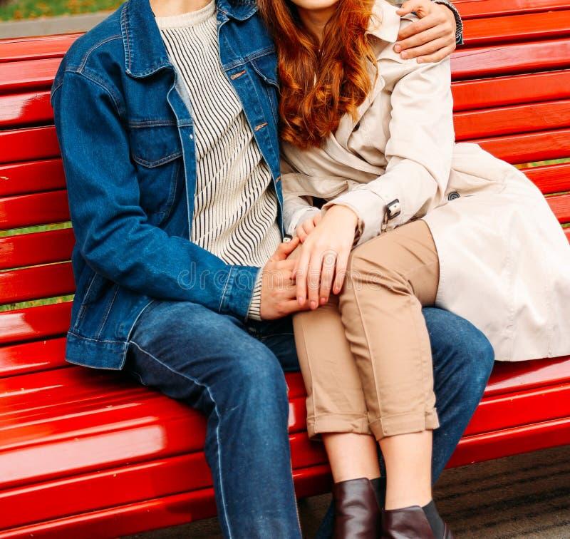 Paarzitting op een bank, benen van een meisje op een kerel, een man die een vrouw koesteren een kerel in jeans en een denimjasje, royalty-vrije stock afbeeldingen