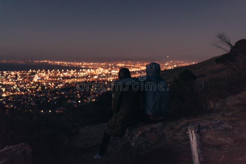Paarzitting op een heuveltop die hieronder cityscape bekijken royalty-vrije stock afbeeldingen